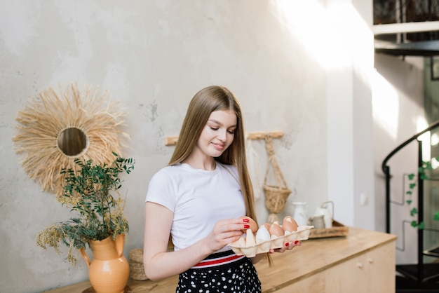 Koncepcja zdrowego odżywiania. piękna młoda kobieta z jajkami w kuchni.