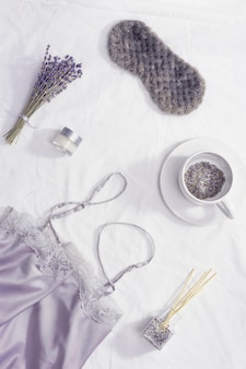 Koncepcja zdrowego snu w nocy, jedwabna piżama, maska do spania, filiżanka lawendowej herbaty, aromaty dla lepszego zasypiania