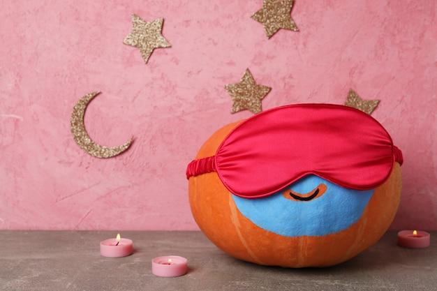 Koncepcja zdrowego snu z dynią na różowym tle