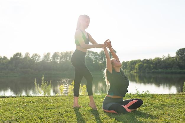 Koncepcja zdrowego stylu życia i ludzi - elastyczne kobiety robiące jogę w letnim parku