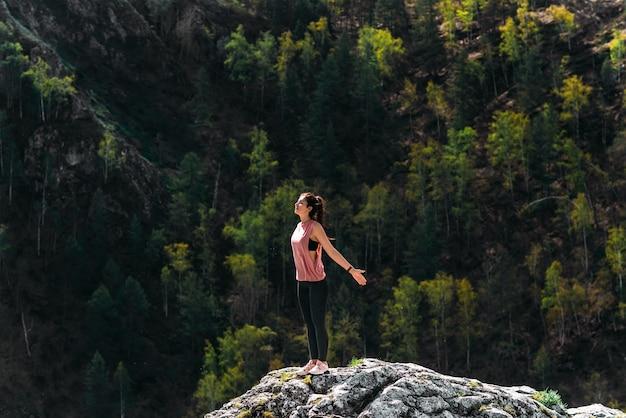 Koncepcja zdrowego stylu życia i relaksu. joga na świeżym powietrzu. szczęśliwa kobieta robi ćwiczenia jogi. medytacja i relaks. kobieta ćwiczy jogę w górach. kobieta medytuje na łonie natury