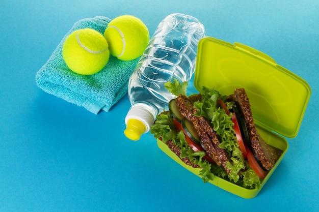 Koncepcja zdrowego stylu życia. sneakers z piłkami tenisów, ręcznik i butelka wody na jasno żółtym tle. skopiuj miejsce.