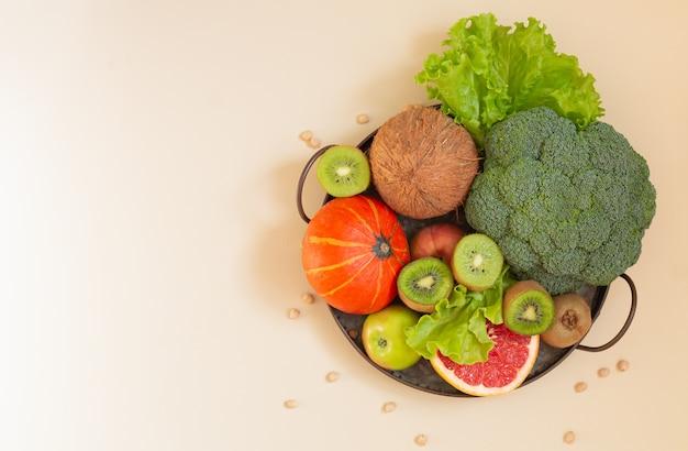 Koncepcja zdrowej, czystej żywności. surowe warzywa i owoce w widoku z góry rustykalnej metalowej tacy