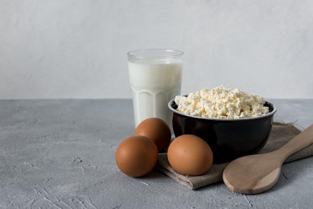 Koncepcja zdrowej żywności, domowy twarożek, szklanka mleka, jogurt i jaja kurze na kamiennym tle, produkty mleczne