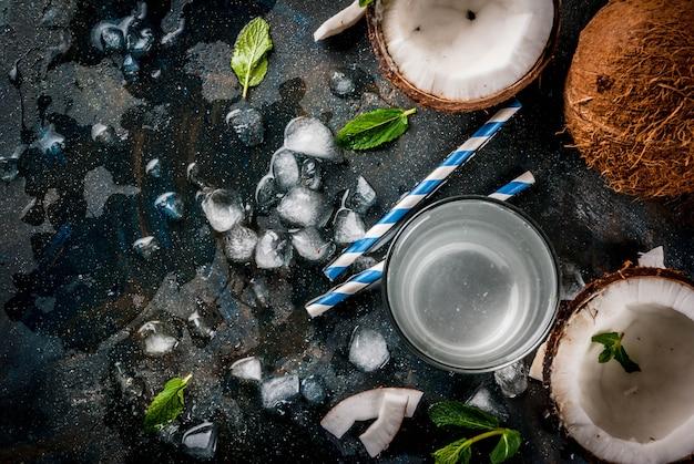 Koncepcja zdrowej żywności. świeża organicznie kokosowa woda z koks kostkami lodu i mennicą na ośniedziałym zmroku - błękitnego tła odgórny widok