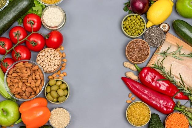 Koncepcja zdrowej żywności, zielone czerwone warzywa, orzechy, mięso z kurczaka na szarym tle