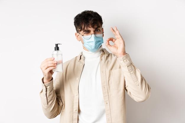 Koncepcja zdrowia covid i kwarantanna portret naturalnego faceta w okularach i masce na twarz pokazującej butelkę ...