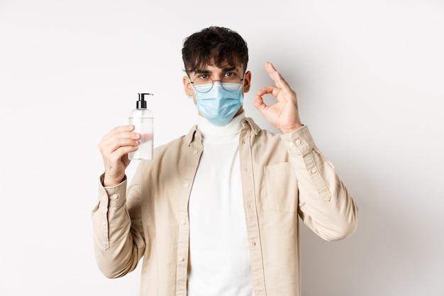 Koncepcja zdrowia, covid i kwarantanny. portret naturalnego faceta w okularach i masce na twarz pokazujący butelkę dobrego środka do dezynfekcji rąk, znak dobra, polecający produkt, biała ściana.