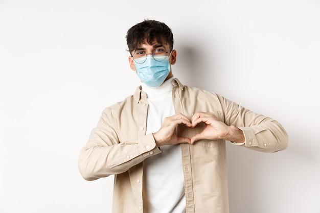 Koncepcja zdrowia, covid i kwarantanny. romantyczny młodzieniec w sterylnej masce medycznej, pokazujący gest serca na piersi, mówi kocham cię, stojąc na białej ścianie.