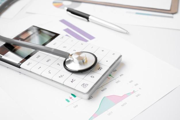 Koncepcja zdrowia finansowego, stetoskop tkający wokół stosów srebrnych i złotych monet oraz kalkulator