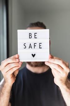 Koncepcja zdrowia i bezpieczeństwa. nierozpoznany mężczyzna trzymający lightbox z tekstem bądź bezpieczny podczas pandemii koronawirusa covid-19