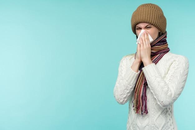 Koncepcja zdrowia i medycyny - młoda kobieta dmuchanie nosa w tkankę, na niebieskim tle. ładna dziewczyna zimna ze smarkaniem.