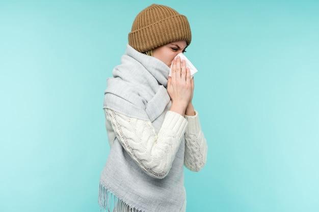 Koncepcja zdrowia i medycyny - młoda kobieta dmuchanie nosa w tkankę, na niebieskim tle