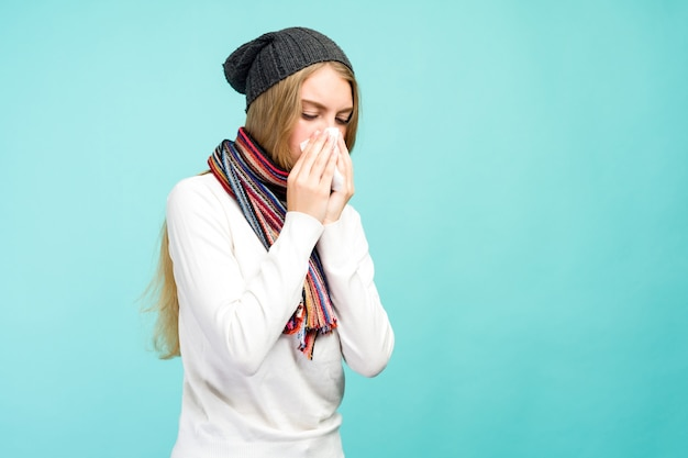 Koncepcja zdrowia i medycyny - sad teen girl dmuchanie nosa w tkanki, na niebieskim tle. ładna dziewczyna zimna ze smarkaniem. - wizerunek