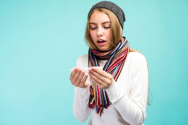 Koncepcja zdrowia i medycyny - sad teen girl dmuchanie nosa w tkanki, na niebieskim tle