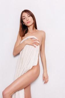 Koncepcja zdrowia, ludzi i urody - piękna kobieta w białym szlafroku po spa. zdjęcie zadbanej kobiety na białym tle. koncepcja odnowy biologicznej i spa.