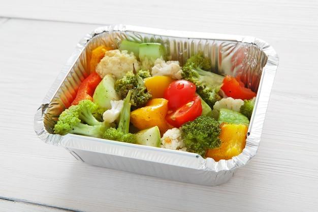 Koncepcja zdrowy obiad i dieta. zabierz jedzenie. warzywa gotowane, takie jak kalafior, brokuły, pomidorki koktajlowe i papryka na białym drewnie