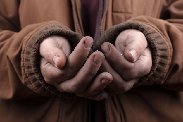 Koncepcja żebraka. biedny człowiek prosi o pomoc pieniężną. srebrne monety w zbliżenie dłoni