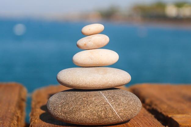 Koncepcja zen. piramida z kamieni na brzegu morza.