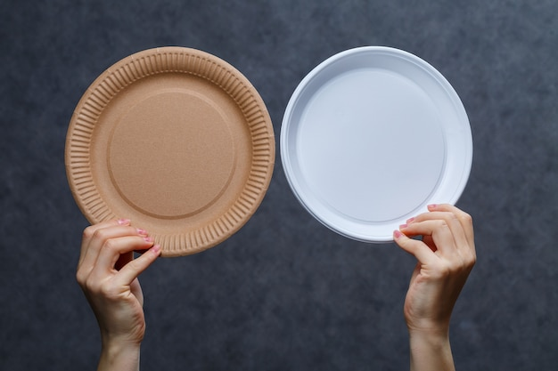Koncepcja zero odpadów. drewniane sztućce a plastikowe sztućce. ekologiczna jednorazowa zastawa stołowa wykonana z drewna bambusowego i papieru na szarym tle. dbanie o środowisko. problem z recyklingiem.