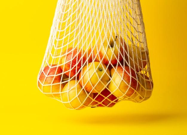 Koncepcja zero odpadów. jabłka w torbie smyczkowej na żółtym tle. brak toreb plastikowych w supermarketach i sklepach