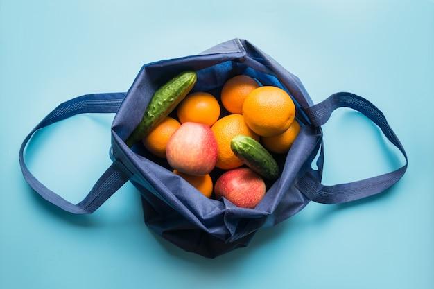 Koncepcja zero odpadów. niebieska tekstylna torba na zakupy ze świeżą pomarańczą i warzywami. miejsce na tekst.