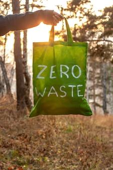 Koncepcja zero odpadów. tekstylna zielona torba z białym napisem w ręku na tle natury i słońca. na tle rozmytych drzew i jesiennej trawy. pionowy. skopiuj miejsce poniżej.