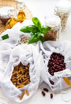 Koncepcja zero waste. eko torebki z fasolą i makaronem. ekologiczna koncepcja zakupów i gotowania, układanie na płasko