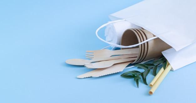 Koncepcja zero waste, ekologiczna biodegradowalna zastawa stołowa i sztućce w papierowej torbie