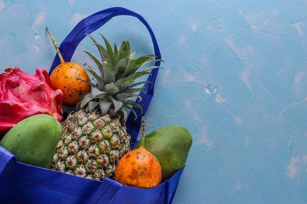 Koncepcja zero waste, niebieska tekstylna torba na zakupy ze świeżymi owocami tropikalnymi: mango, ananasem, smokiem i marakują, orientacja pozioma