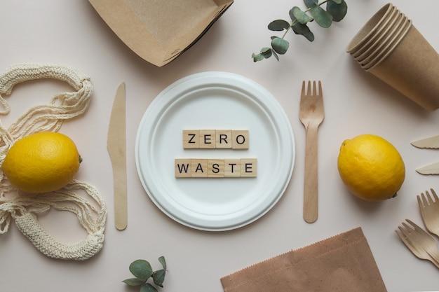 Koncepcja zero waste. noże, widelce, talerz, worek strunowy, worek papierowy i napis zero waste