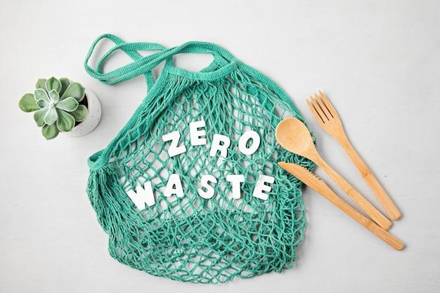 Koncepcja zero waste. zestaw ekologicznych bambusowych sztućców, bawełniana torba z siateczki, kubek do kawy wielokrotnego użytku. zrównoważone, etyczne zakupy, styl życia bez plastiku. widok z góry, płaski układ.