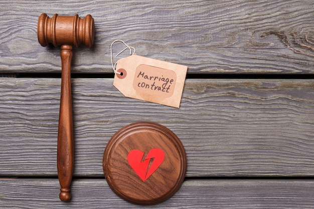 Koncepcja zerwania umowy małżeńskiej. drewniany młotek ze złamanym sercem na drewnianym biurku.