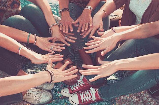 Koncepcja zespołu i przyjaźni z tłumem rąk i stóp razem dotykających się i współpracujących - kaukascy przyjaciele korzystający z wypoczynku na świeżym powietrzu - hipisowska miłość