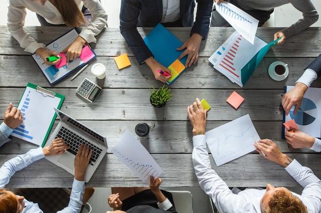 Koncepcja zespołu planowania zarządzania przedsiębiorstwem, ludzie siedzący przy stole w biurze i pracujący z raportami danych finansowych