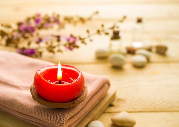 Koncepcja zestawu spa aromaterapii. świeca na różowym ręczniku z rozmyciem obrazu olejku do masażu i kamyków.