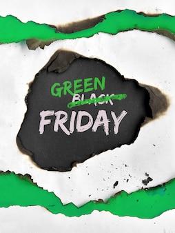 """Koncepcja zielonego piątku z dziurą spaloną w białym papierze. tekst """"wyprzedaż w czarny piątek"""" z wykreślonym słowem """"czarny"""", zamiast niego zamiast """"zielony""""."""