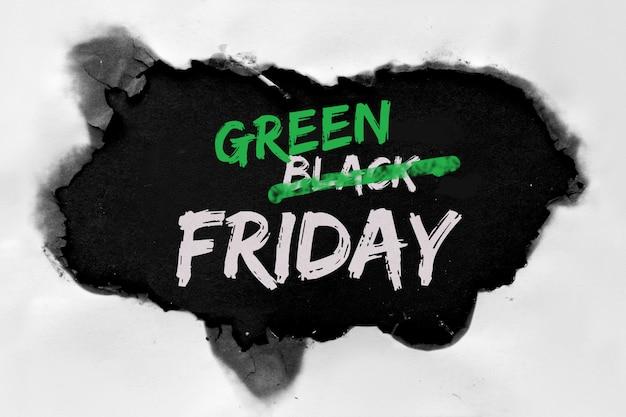 """Koncepcja zielonego piątku z dziurą wypaloną w białym papierze. tekst """"wyprzedaż w czarny piątek"""" z wykreślonym słowem """"czarny"""", zamiast niego zamiast """"zielony""""."""