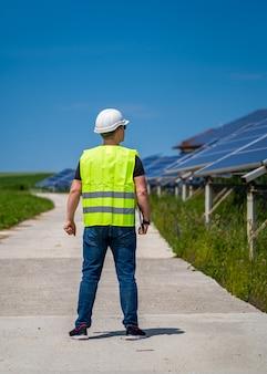 Koncepcja zielonej nowej energii. inżynier w elektrowni słonecznej. widok z tyłu.