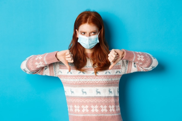 Koncepcja zima, covid-19 i pandemia. nastrojowa ruda dziewczyna w masce pokazującej kciuki w dół, z dezaprobatą i niechęcią, stojąca na niebieskim tle.