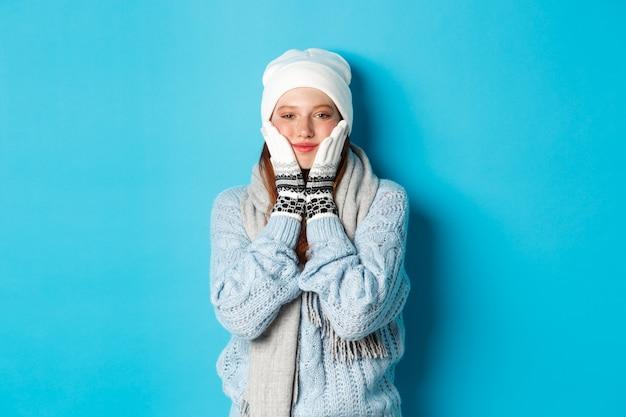 Koncepcja zima i święta. śliczna dziewczyna w białej czapce, swetrze i rękawiczkach, ściskając policzki i uśmiechając się zadowolona, rozgrzewka po mrozie na świeżym powietrzu, stojąc na niebieskim tle