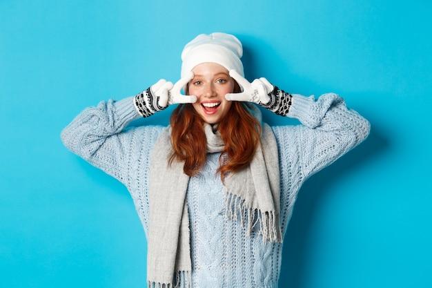 Koncepcja zima i wakacje. śliczna ruda nastolatka w beani, rękawiczkach i swetrze pokazującym znak pokoju, patrząc w lewo w kamerę i życząc wesołych świąt, stojąc na niebieskim tle.