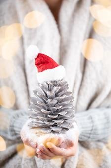 Koncepcja zima młode ręce trzymając wystrój świąteczny. pomysł na świąteczne dekoracje. boże narodzenie wystrój w rękach kobiety, tło z złotym bokeh.