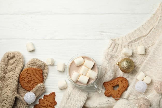 Koncepcja zima sweter, kawa z ptasie mleczko i ciasteczka na podłoże drewniane