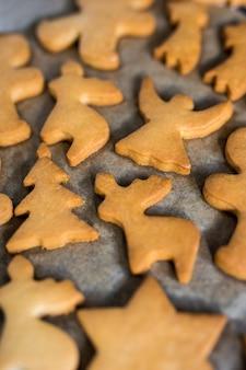Koncepcja zimowa - zbliżenie kształtowanych ciasteczek lub pierników w gorącym piekarniku