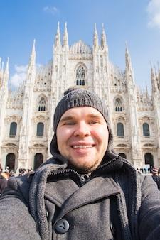 Koncepcja zimowych podróży, wakacji i wakacji - młody zabawny człowiek robi selfie w pobliżu katedry w mediolanie duomo di milano, włochy.
