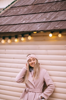 Koncepcja zimowych świąt bożego narodzenia uśmiechnięta dziewczyna w płaszczu pozuje w pobliżu sylwestrowych girland