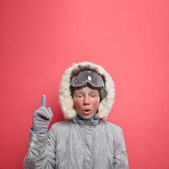 Koncepcja zimowych wakacji. zszokowana zamarznięta młoda kobieta trzyma szeroko otwarte usta i wskazuje powyżej oszołomiona bardzo niską temperaturą i obfitymi opadami śniegu, jeżdżąc na nartach w grudniu ubrana w odzież wierzchnią