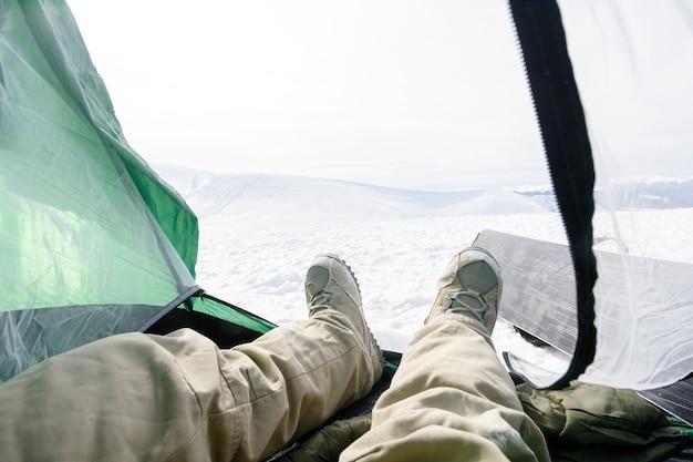 Koncepcja zimy, wypoczynku, sportu i ludzi - snowboardzista leży w namiocie. miłość do szczytu chłopca, miłość do obozu i góry