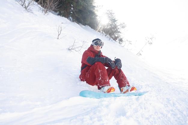 Koncepcja zimy, wypoczynku, sportu i ludzi - snowboardzista siedzi wysoko w górach na skraju stoku i spogląda w dal.